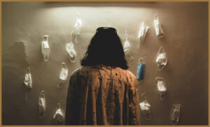 An autistic woman looking at a wall of empty masks